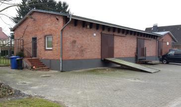 Das Bild zeigt den ehemaligen Genossenschaftsschuppen in der Harmstorfer Straße heute. Er wird mittlerweile als Wohnhaus und Gewerbebetrieb genutzt.